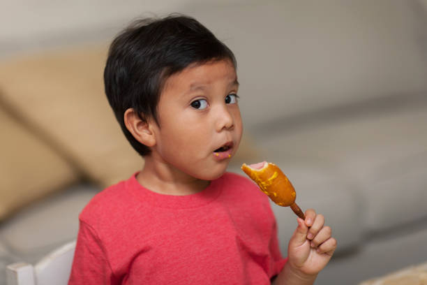A young boy looks with awe as he takes a bite out of a homemade corn dog, a healthy snack. stock photo