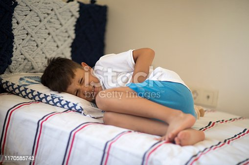 Young boy lying in bed with stomachache