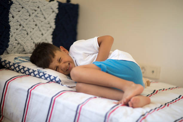 Young boy lying in bed with stomachache stock photo