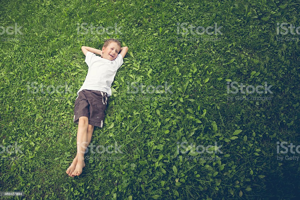 Young boy lying in the grass and laughing stock photo