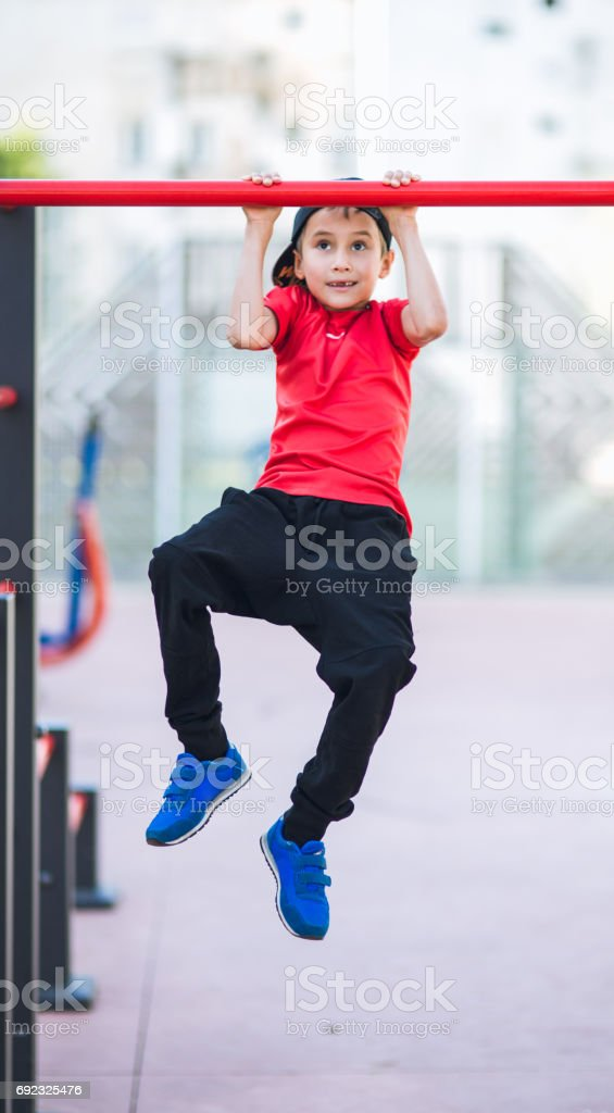 Young boy make sport workout on the street in real life