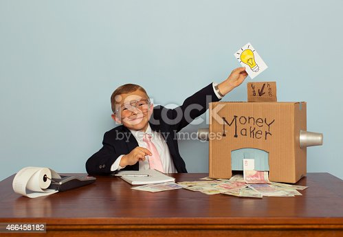 A young boy and businessman feeds his money making machine with great ideas and out comes lots of British Pounds Sterling. Bling. Boy dressed in business suit. Retro styled.