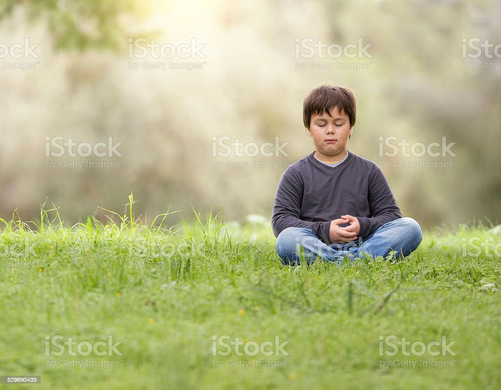 young boy meditating in nature. 7 year old child.