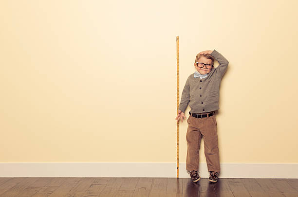 young boy nerd measures height and is tall - height measurement stock photos and pictures