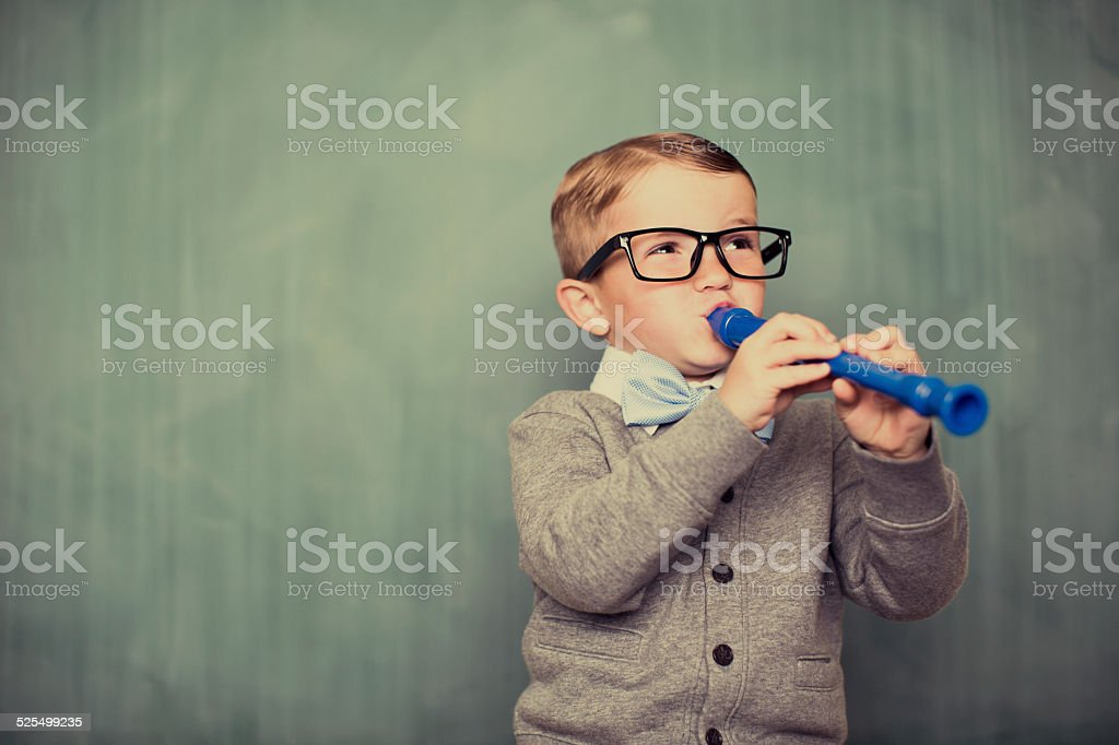 Young Boy Nerd Plays Recorder in Classroom stock photo