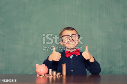 istock Young Boy Nerd Saves Money in His Piggy Bank 482805813