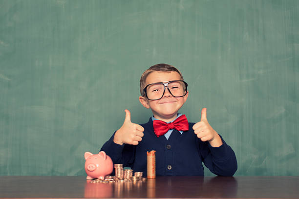 Young Boy Nerd Saves Money in His Piggy Bank A young boy is excited about saving money for the future.  miserly stock pictures, royalty-free photos & images