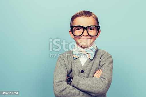 A young boy dressed as a nerd with glasses is looking in the camera with a big smile on his face. He has a bow tie on and is in front of a blue wall.