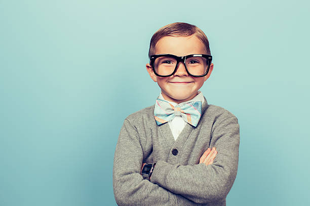 Young Boy Nerd with Big Smile A young boy dressed as a nerd with glasses is looking in the camera with a big smile on his face. He has a bow tie on and is in front of a blue wall. child prodigy stock pictures, royalty-free photos & images