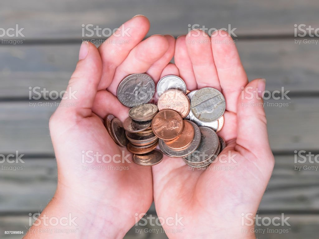 Young boy offers collection of US coins in cupped hands stock photo