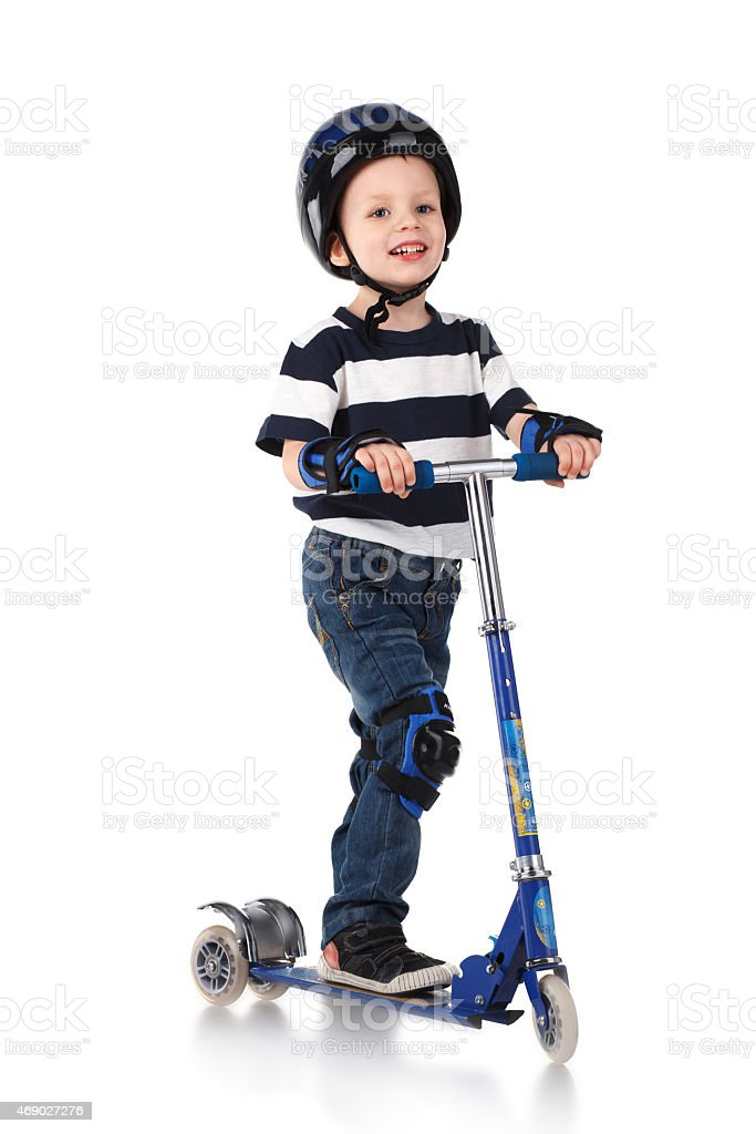 Young boy on a scooter with helmet, wrist and knee pads stock photo