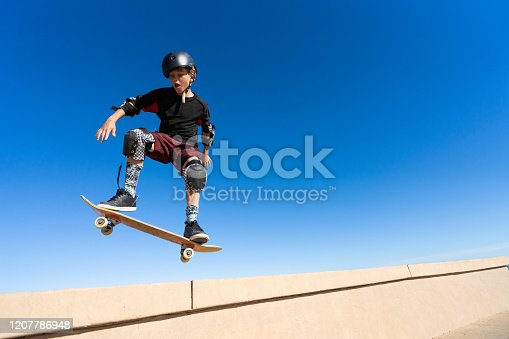 Young Boy on A Skateboard Jumping Into the Air.  Isolated on the blue sky.