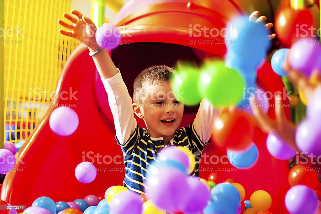 A young boy on a slide playing in a ball pit stock photo