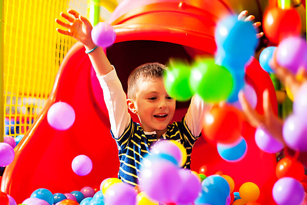kleine junge in der ball-pool - kinderspielplatz stock-fotos und bilder