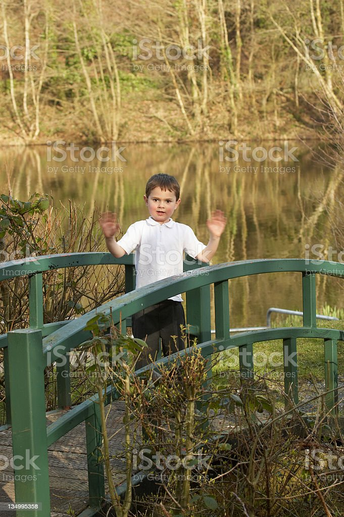 Young boy on countryside footbridge royalty-free stock photo