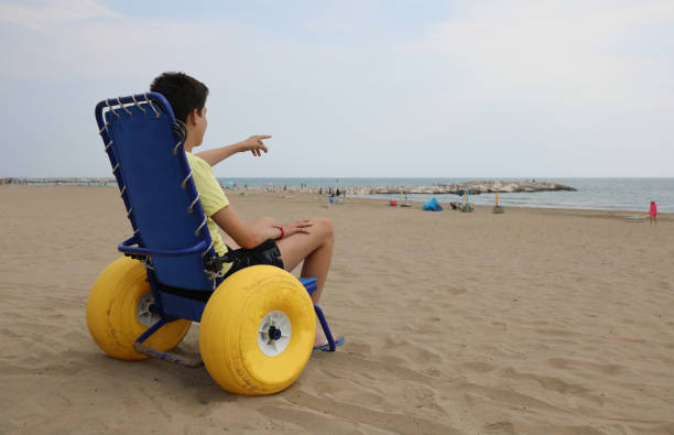 young boy on the special wheelchair with big inflatable wheels t stock photo