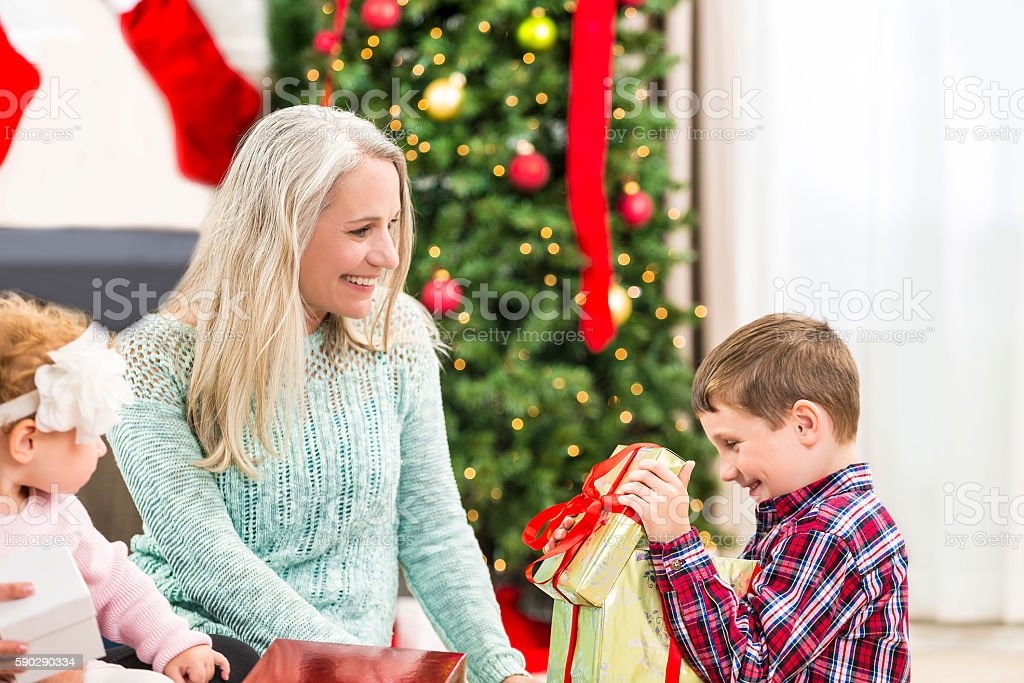 Young boy opening gift with his excited grandmother looking on royaltyfri bildbanksbilder