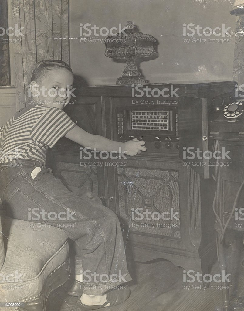 Young Boy Operating a Radio in His Living Room royalty-free stock photo