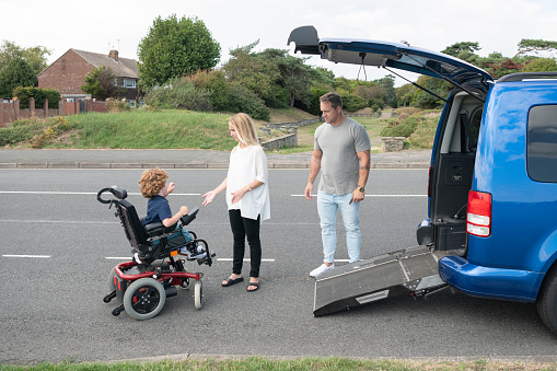 6 year old child with muscular dystrophy steering his electric wheelchair to gain access to family car, mother and father assisting and encouraging