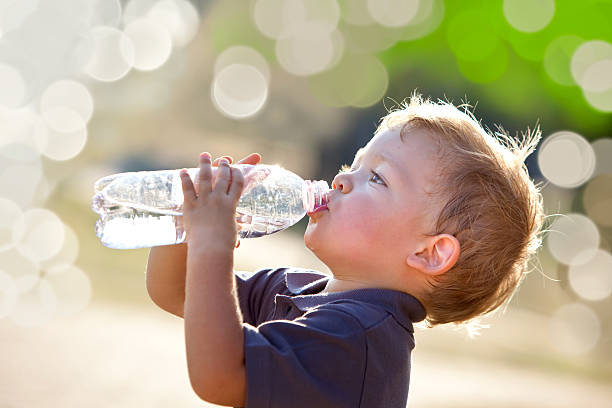 Young boy outside, drinking from a water bottle stock photo