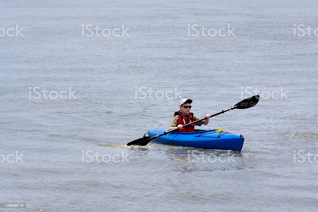 Young Boy Paddles Kayak on the water stock photo