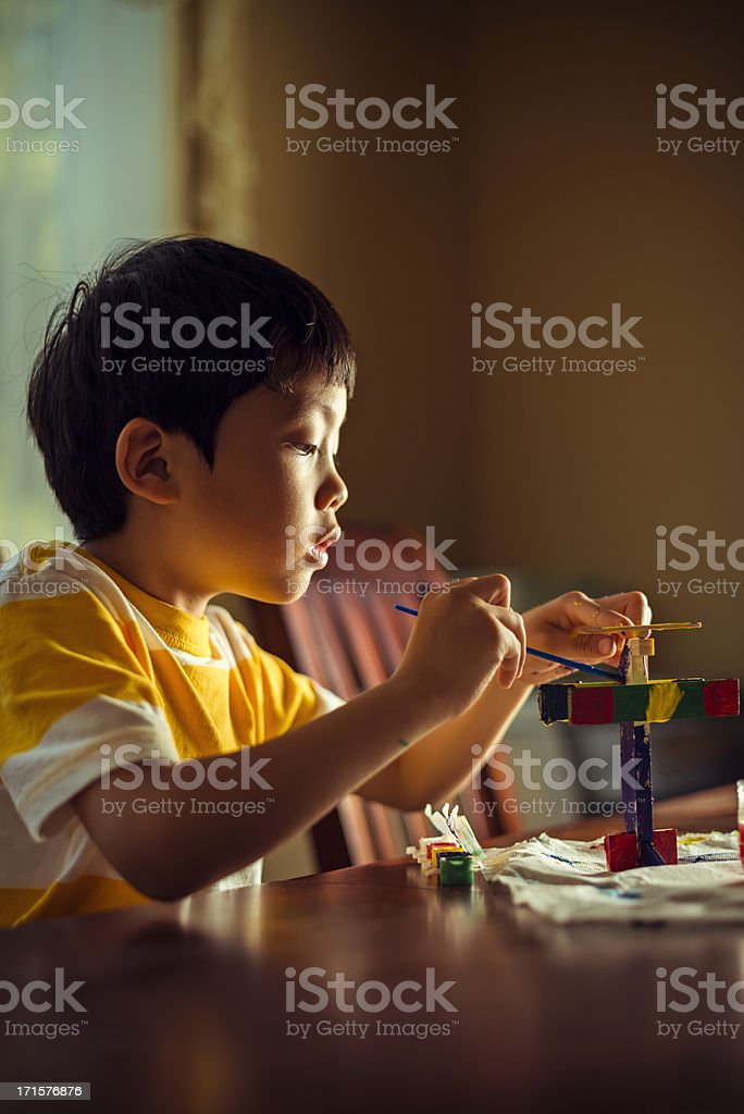 Young boy painting wooden airplane royalty-free stock photo