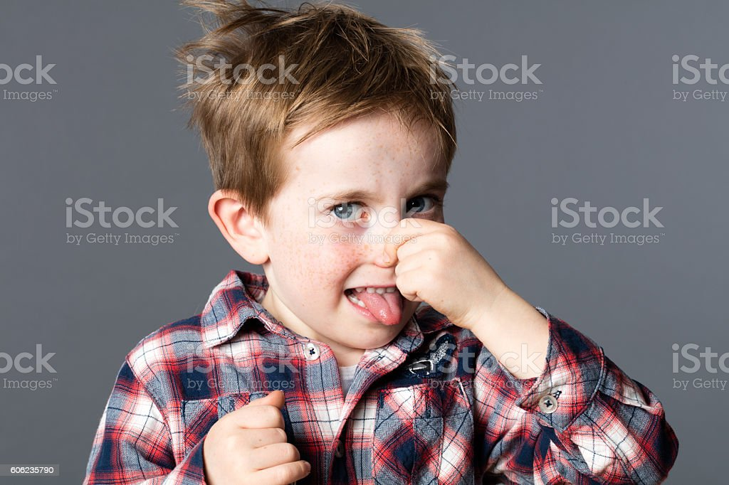young boy pinching his nose for sign of bad odor stock photo