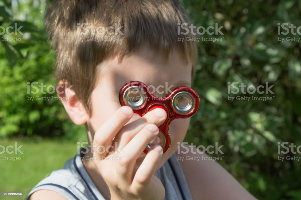 Young boy play with red fidget spinner in outdoors, focus on spinner. stock photo