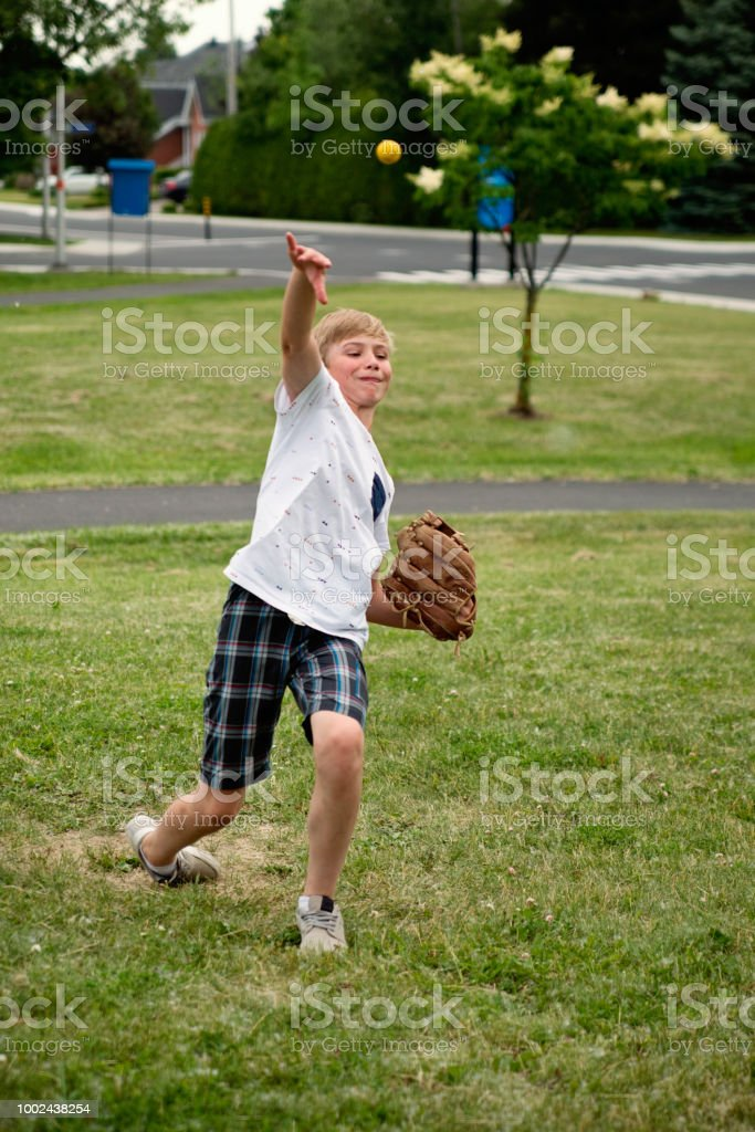 Young boy playing baseball in suburb park. stock photo