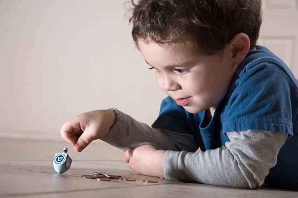 Young boy playing Dreidel, lying on a linoleum floor stock photo