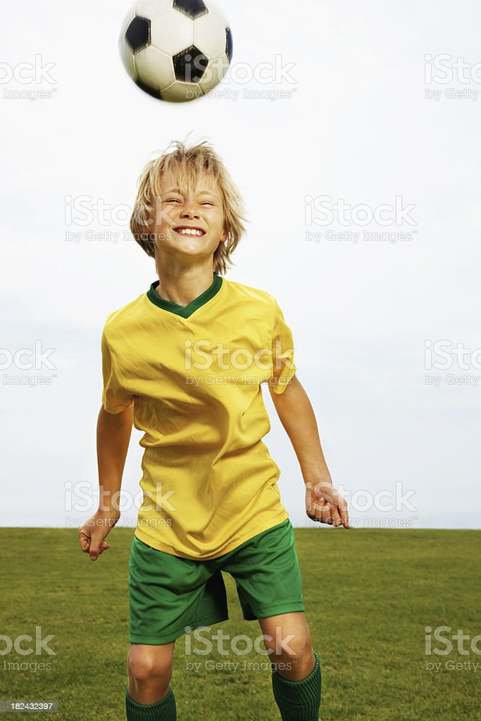 Young boy playing football against clear sky royalty-free stock photo