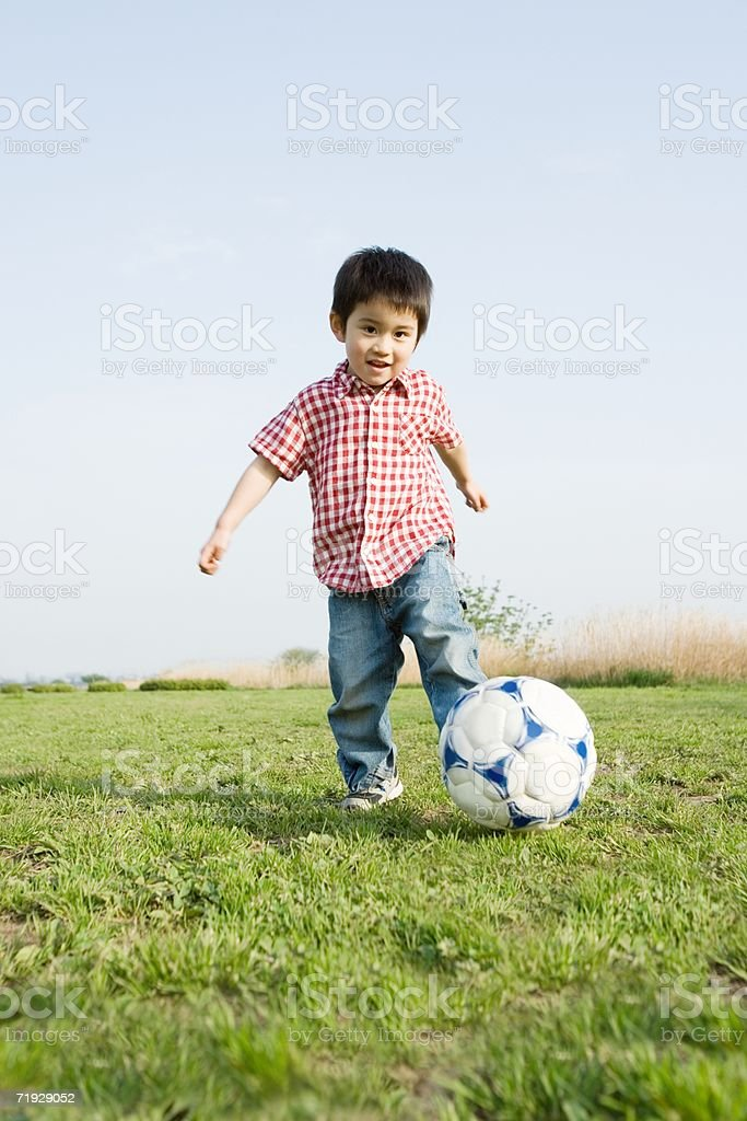 Young boy playing football stock photo