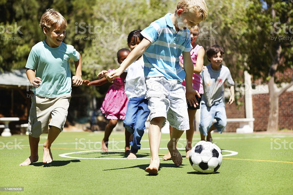 Young boy playing football with friends royalty-free stock photo
