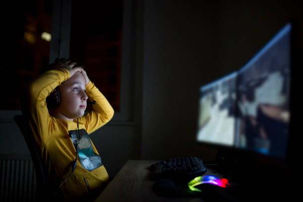 Young boy playing games on a computer at home stock photo