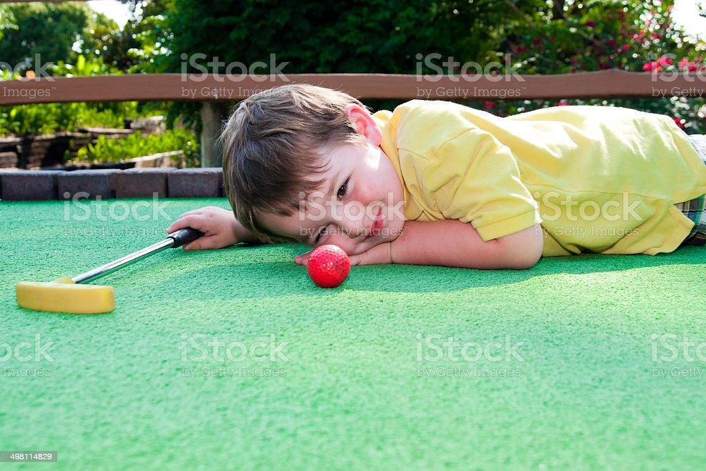Young boy playing mini golf stock photo