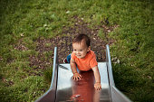 An adorable baby boy is climbing up a slide in the park looking happy and full of vitality.