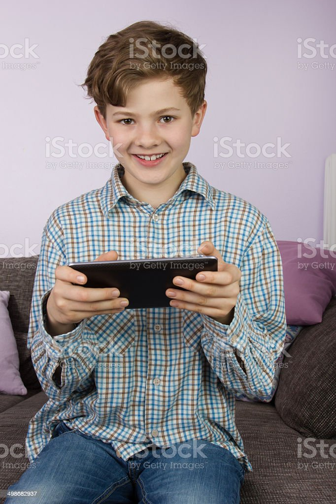Young boy playing on tablet, game console and laptop stock photo
