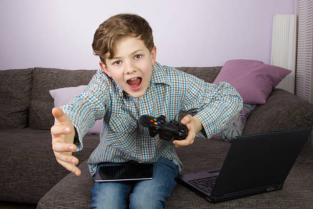 young boy playing on tablet, game console and laptop - cursed stock pictures, royalty-free photos & images