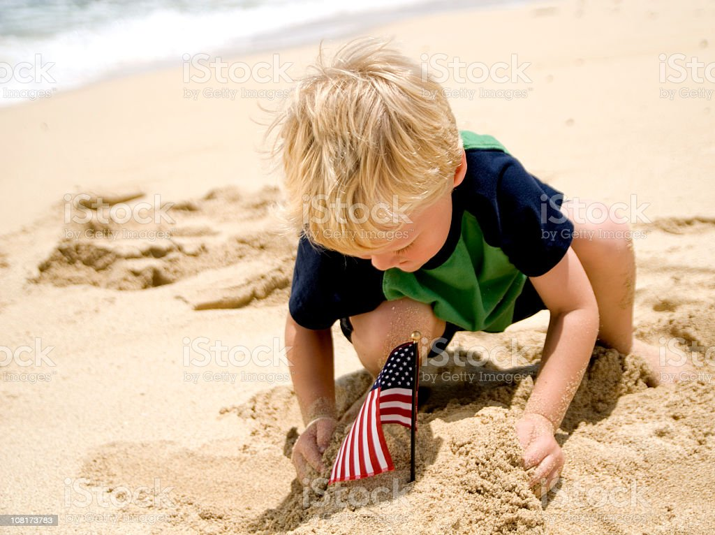 Young boy playing on the beach by an American flag  royalty-free stock photo