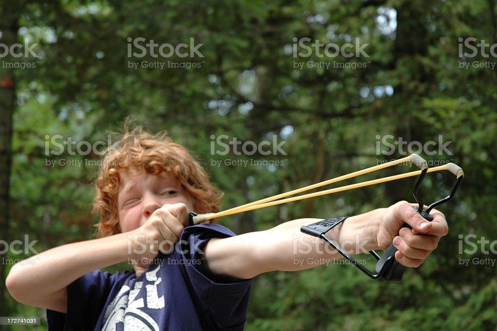 Young boy playing outside with slingshot  stock photo