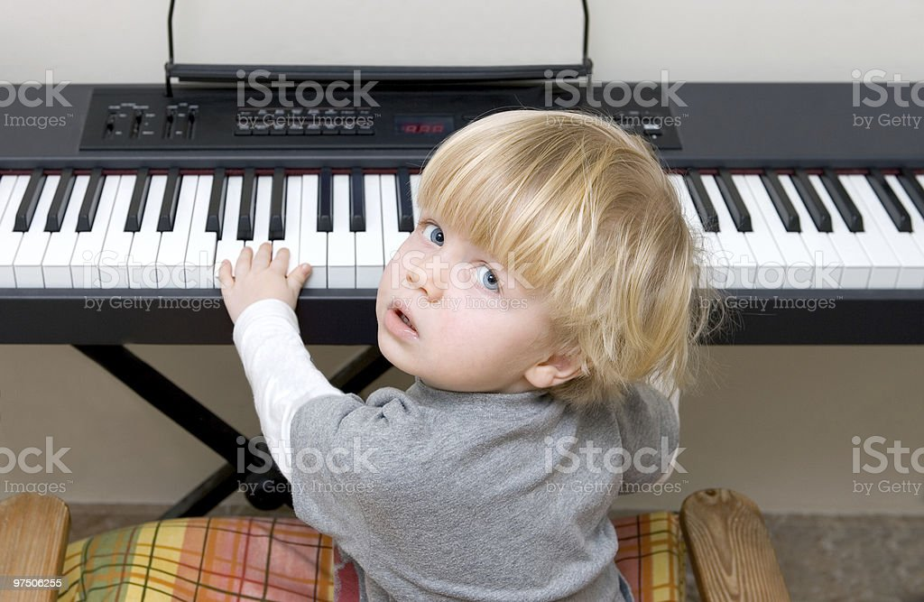 Young boy playing piano or keyboard royalty-free stock photo