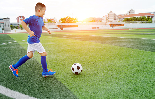 Young boy playing soccer ball on the field