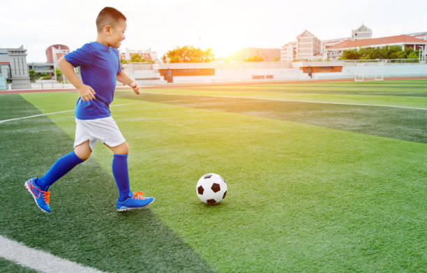 Young boy playing soccer ball on the field stock photo