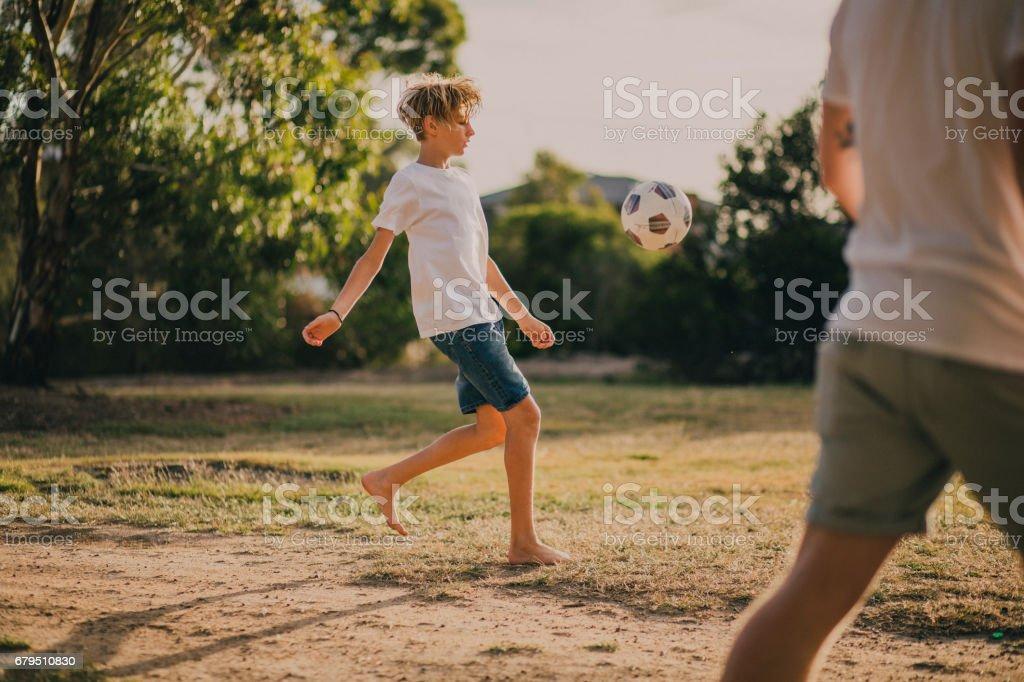 Jeune garçon jouant au Soccer dans le parc - Photo