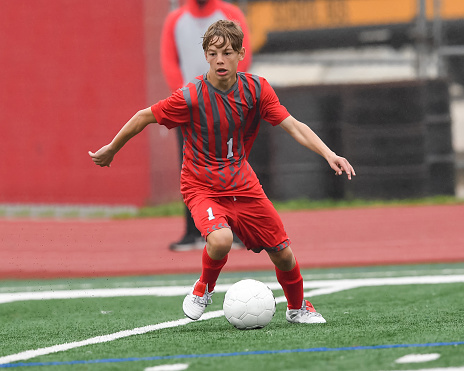High school age boy displaying exceptional skills while playing soccer