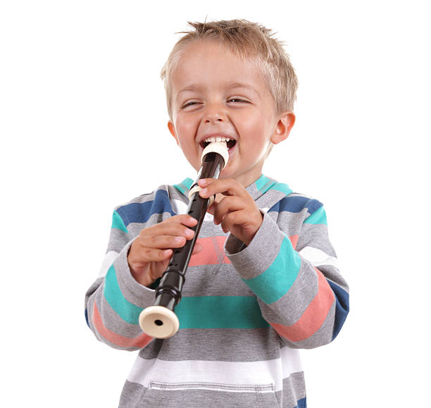 a young boy playing the recorder - recorder stock photos and pictures
