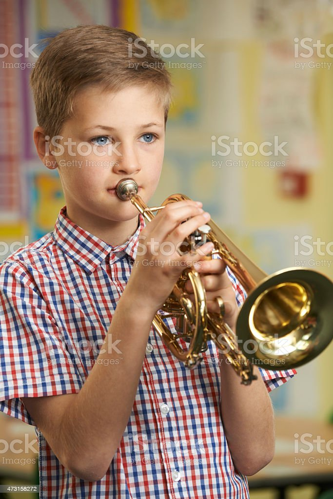 Young boy playing the trumpet in school music lesson stock photo
