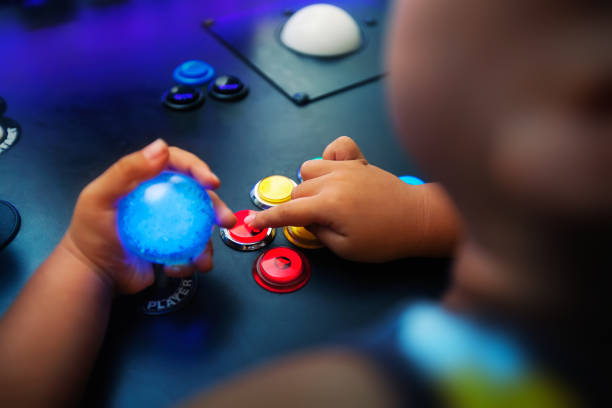 A young boy playing video games on a home arcade with push buttons arranged in a fighter style layout. stock photo