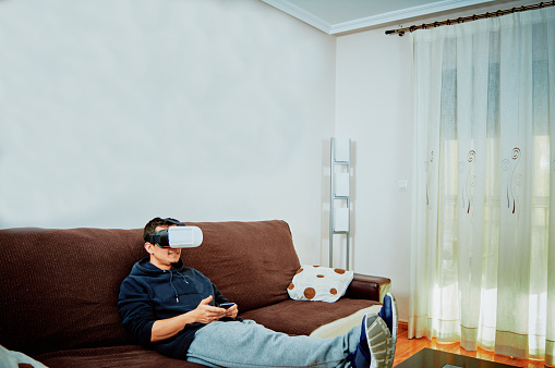istock Young boy playing video games with 3d glasses 1141187755