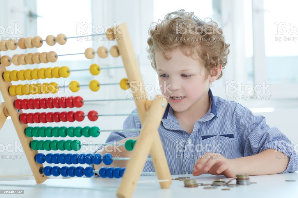 Young boy playing with counter and coins. The concept of children's economic education. stock photo